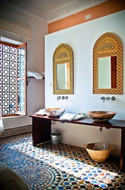 a colorful Moroccan bathroom with oranted mirrors, painted bowl sinks, a tiled floor and a cool window