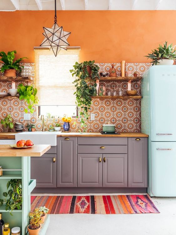 a colorful boho kitchen with a bright orange wall, a mint fridge, grey cabinets with a wooden top and a printed tile backsplash