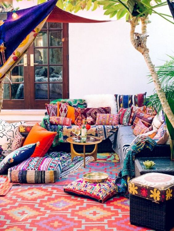 a colorful boho patio with bright pillows and ottomans plus rugs, a colorful canopy and a small gilded coffee table