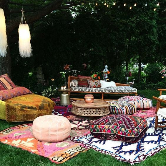 a colorful boho patio with ottomans, cushions, pillows, rugs, rattan furniture and long fringe lamps