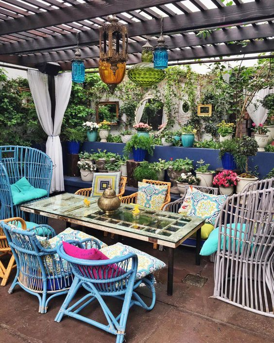 a colorful boho patio with rattan chairs in various colors, colorful pillows, bright glass lanterns and a simple table