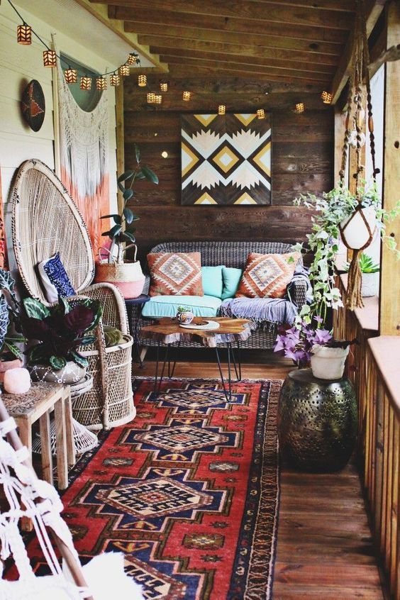a colorful boho patio with wicker and wooden furniture, folksy artworks, lights, fringe, macrame and boho rugs