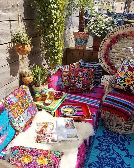 a colorful boho patio with wicker furniture, printed and bright textiles, potted cacti and plants