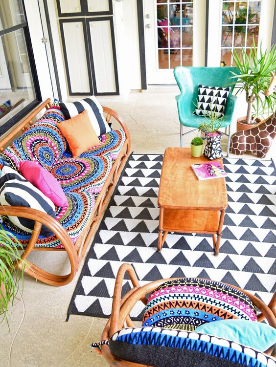 a colorful boho space with rattan furniture, colorful pillows and tetiles, a printed rug and potted plants