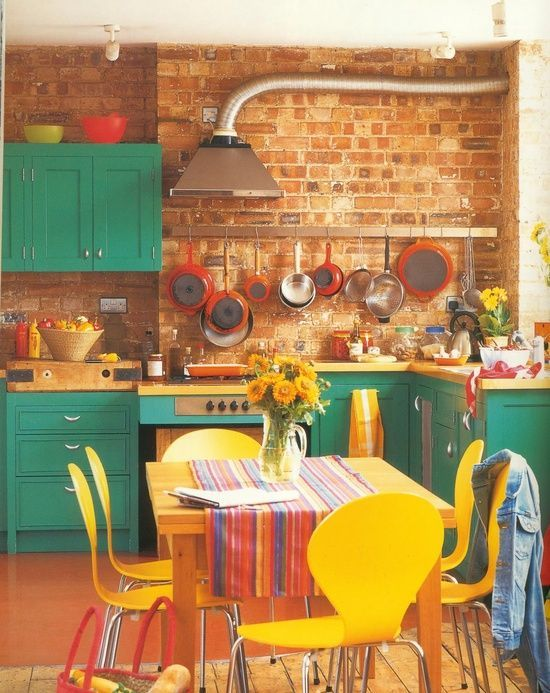 a colorful kitchen with emerald cabinets, yellow chairs, printed textiles and red pans and tableware