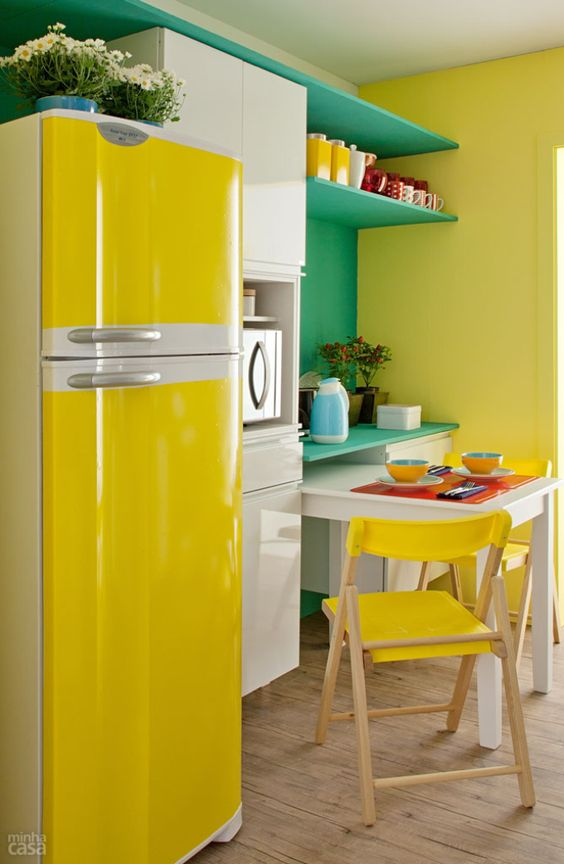 a colorful kitchen with white cabinets, a minty green storage unit, yellow chairs and a fridge plus more yellow touches
