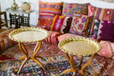 a colorful living room with bright textiles and patterns, gold tables and a macrame hanging