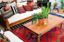 a colorful living room with lots of pillows and rugs, potted plants and mosaic pendant lamps