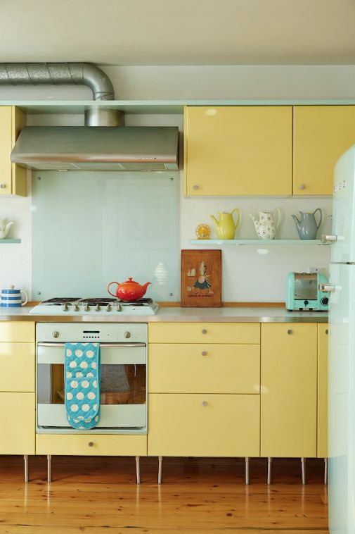 a colorful modern kitchen with yellow cabinets, a mint glass backsplash, a mint fridge and a cooker is fun