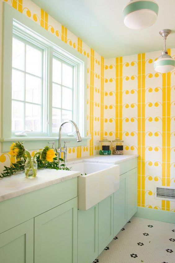 a colorful welcoming kitchen with yellow print wallpaper walls, a mint frame window and mint cabinets for a bold look