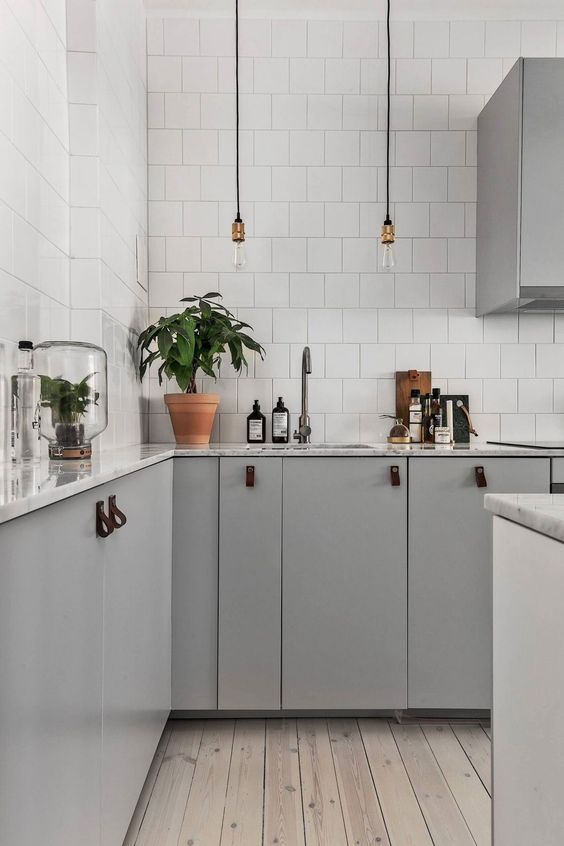 a contemporary Scandinavian kitchen with grey cabinets with leather pulls, bulbs, white tiles and a wooden floor