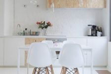 a contemporary Scandinavian kitchen with white and plywood cabinets, bulbs hanging from above and a sleek dining set