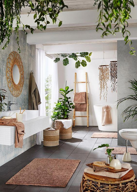 a contemporary meets boho space with potted greenery, baskets, rattan furniture, a wicker mirror and a ladder