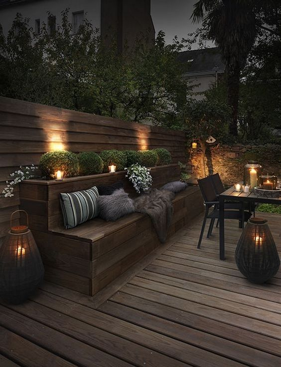 a contemporary meets rustic patio with wooden furniture, candle lanterns, boxwood and blooms
