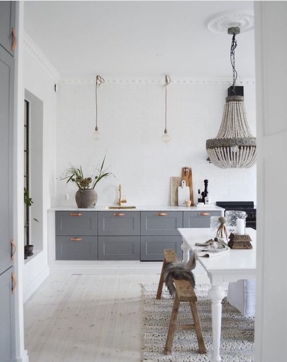 a contemporary meets vintage kitchen with grey cabinets, pendant lamps and a chandelier, a white vintage table and benches