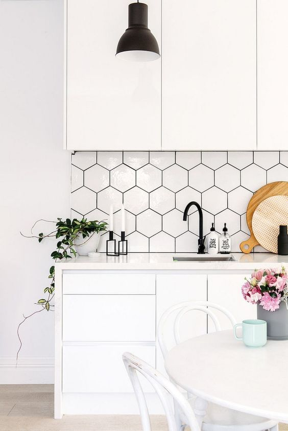 a contemporary white kitchen with sleek cabinets, hex tiles with black grout, black hardware and blooms