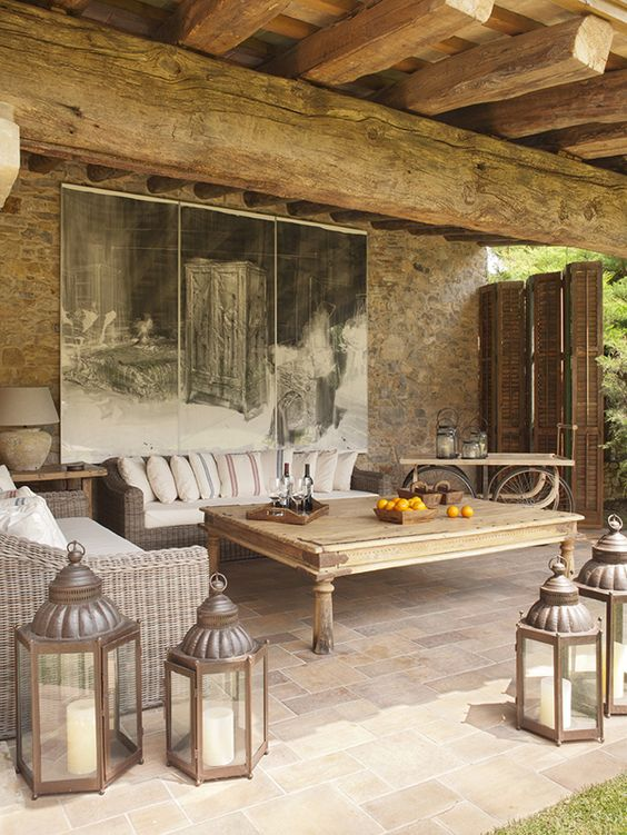 a countryside patio with wicker and wooden furniture, candle lanterns, an artwork and a shutter screen