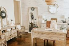 a cozy rustic home office with white beadboard, wooden furniture, a mirror, a pendant lamp and lots of greenery