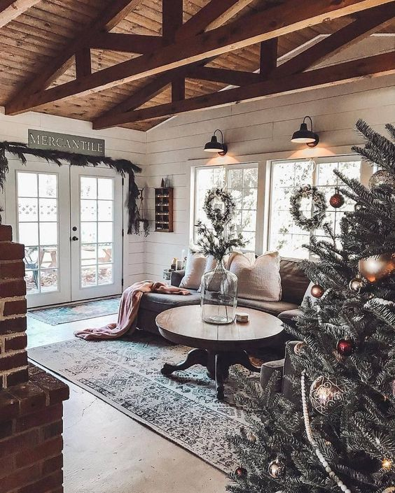 a cozy rustic living room with a round wooden table, a brick fireplace, a wooden ceiling with beams and an evergreen garland