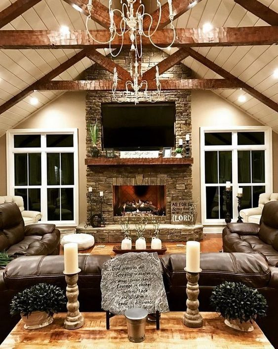 a cozy rustic living room with beams on the ceiling, a stone clad fireplace, a large leather sofa and candles