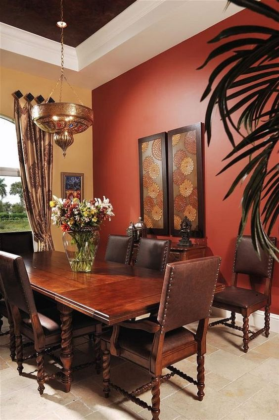 a dark dining space with a red accent wall, a dark heavy carved table, leather chairs and a metal Moroccan lamp that creates a mood
