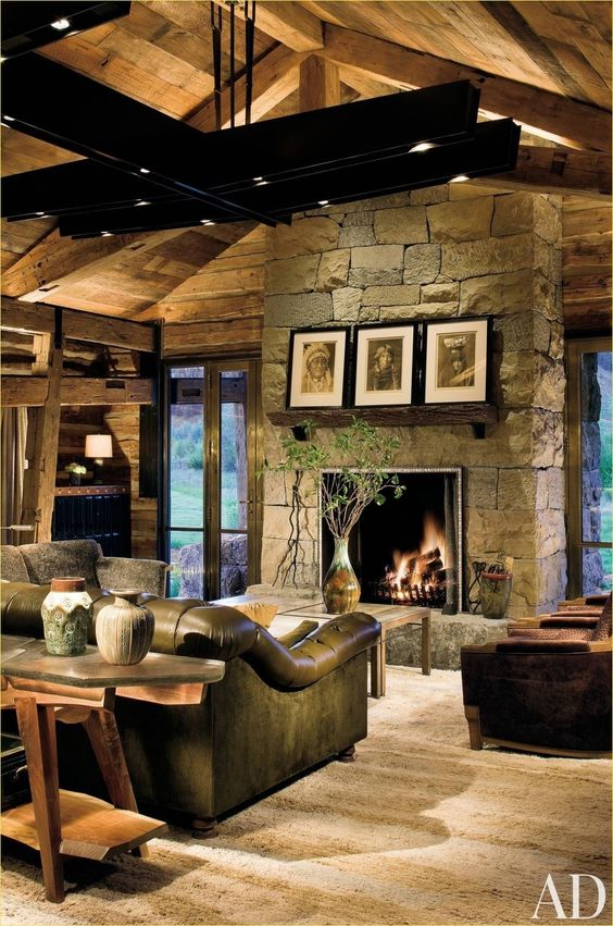 a dark rustic living room with a stone clad fireplace, wooden beams on the ceiling and leather furniture that make the space cozier