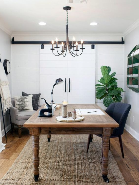 a farmhouse home office with a vintage desk, a jute rug, a grey chair, a clock and a vintage chandelier plus statement plants