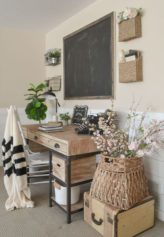 a farmhouse home office with a wooden desk, a chalkboard, baskets on the wall, a basket with flowers on a suitcase