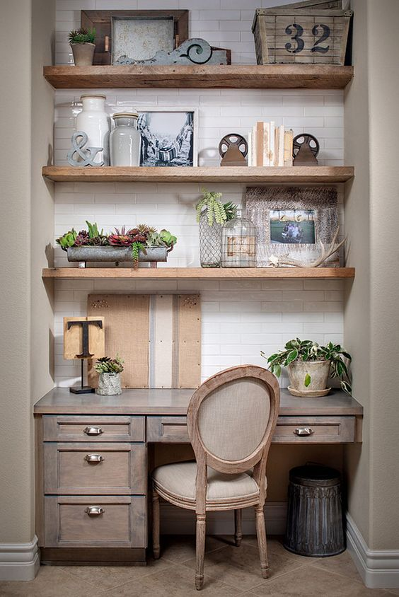 a farmhouse home office with open shelving, a rustic desk, a vintage chair, greenery in pots and artworks