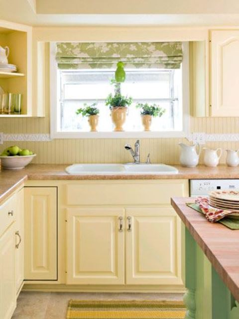 a farmhouse kitchen with light yellow cabinets and a beadboard backsplash, a green kitchen island and a green printed curtain