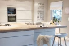 a glam Scandinavian kitchen with sleek cabinets, a storage kitchen island with a woodne countertop, wooden stools and lights