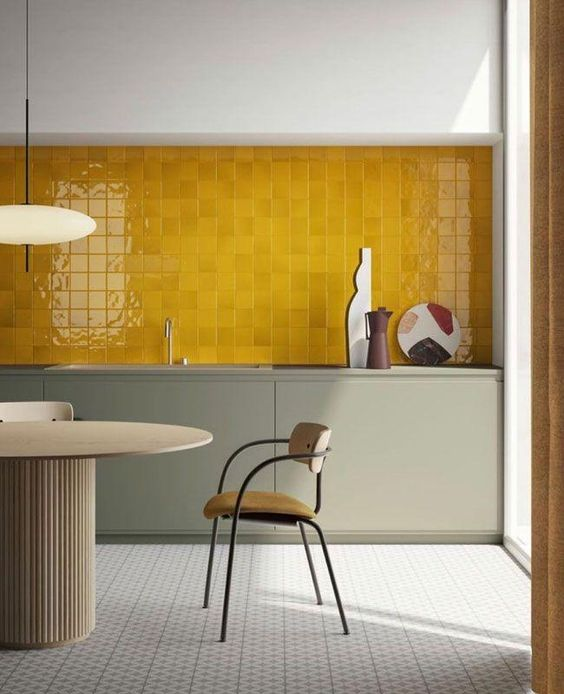 a gorgeous minimalist kitchen with grey green sleek cabients and a mustard tile backsplash plus wooden dining furniture