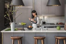 a grey Scandinavian kitchen with sleek lit up cabinets, pendant lamps, white stone countertops and a backsplash