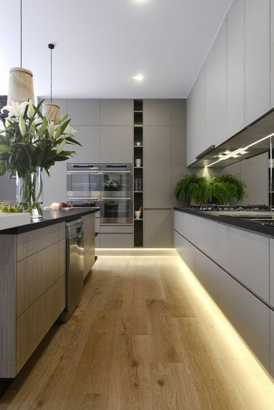 a grey minimalist kitchen with sleke cabinets, black countertops, built-in lights and pendant lamps