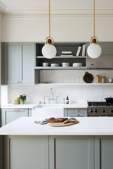 a grey vintage-inspired kitchen with paneled cabinets, white tiles and countertops and pendant lamps
