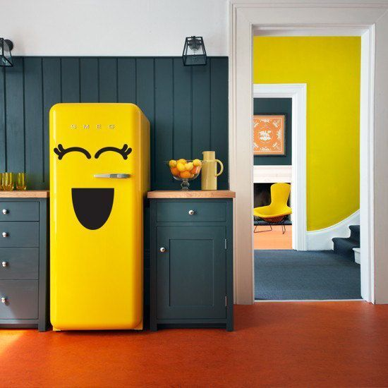 a hunter green kitchen with a bold yellow Smeg fridge looks extra bold and fun, it's pure modern chic