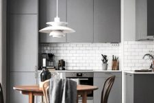 a laconic minimalist kitchen with grey sleek cabinets, a wooden dining set, a pendant lamp and additional lights