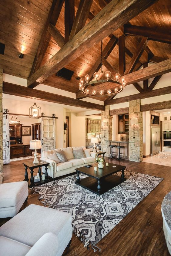 a large rustic living room with an attic ceiling and beams, stone clad pillars and a stained wooden floor
