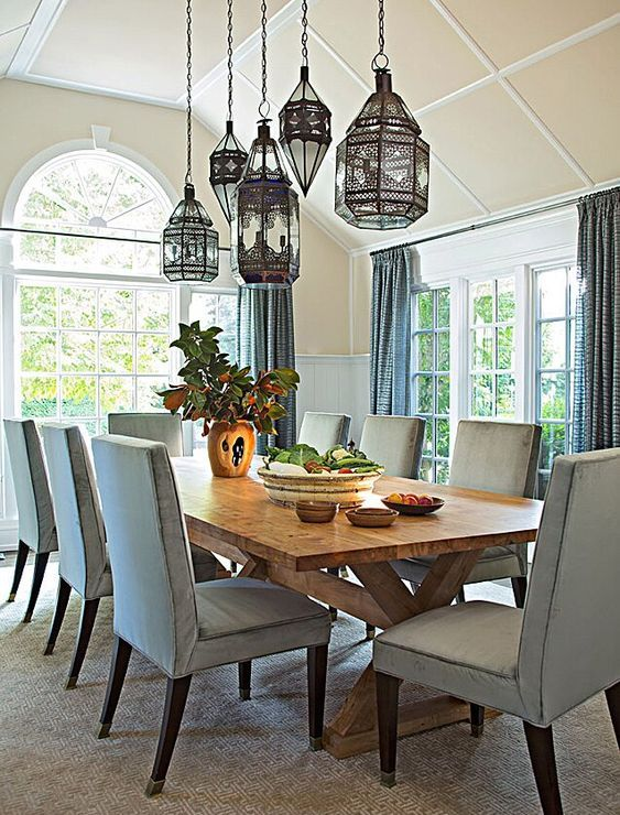a lovely blue dining room with paneling on the walls, a wooden trestle table and pale blue chairs plus a cluster of pendant Mrooccan lamps