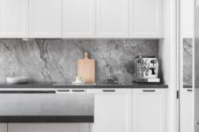 a minimal Nordic kitchen with white paneled cabinets, a grey stone backsplash, black countertops and a wooden floor