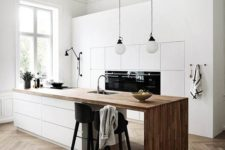 a minimalist Nordic kitchen with sleek white cabinets, a sleek white kitchen island with a wooden waterfall countertop and pendant lamps