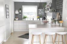 a minimalist Scandi kitchen with grey walls, sleek white cabinets, stools and pendant lamps