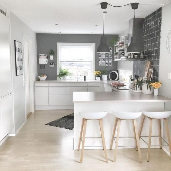a minimalist Scandi kitchen with grey walls, sleek white cabinets, stools and pendant lamps