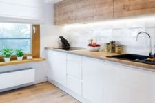 a minimalist Scandi kitchen with wooden upper cabinets, sleek white lower ones, a windowsill shelf and built-in lights