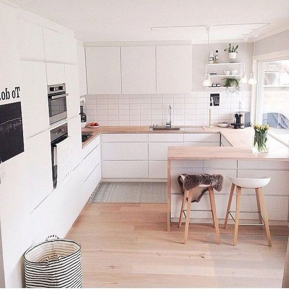 a minimalist Scandinavian kitchen with sleek white cabinets, light staiend countertops, stools and built in appliances