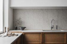 a minimalist Scandinavian kitchen with sleek white uppers, paneled wood lower cabinets, a stone backsplash and countertops