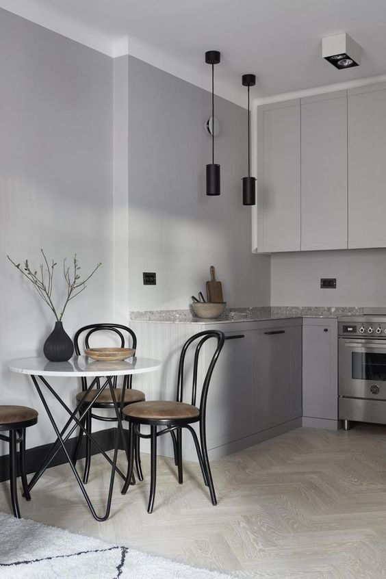 a minimalist grey Nordic kitchen with black pendant lamps, a grey stone countertop and a table with hairpin legs