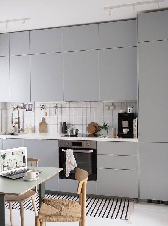 a minimalist grey kitchen, white tiles, woven chairs and a simple and small dining table