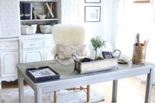 a modern farmhouse home office with a white storage unit, a pale desk, a vintage sphere lamp and faux fur