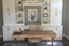 a modern farmhouse home office with a white storage unit, a wooden trestle desk and a comfy chair plus a gold chandelier